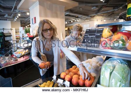La donna a fare la spesa e preleva le arance nel mercato Foto Stock