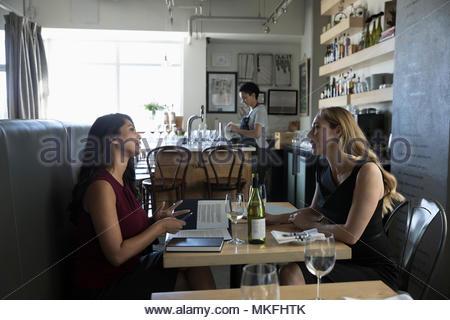 Imprenditrici parlando, godendo di vino al pranzo di lavoro cafe Foto Stock