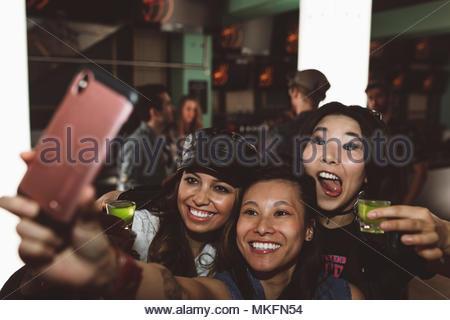 Giocoso, esuberante giovane femmina amici millenario scattare istantanee e tenendo selfie in discoteca Foto Stock