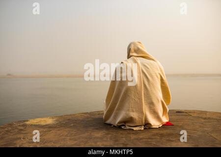 Un santo uomo vestito di bianco è di pregare e meditare su uno dei tanti Ghats di Varanasi davanti al fiume sacro Gange, India. Foto Stock