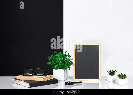 Telaio in legno nero con posto per il testo. Mock up. Elegante sala interna. Pianta verde in un vaso bianco su bianco-nero e sfondo a parete Foto Stock