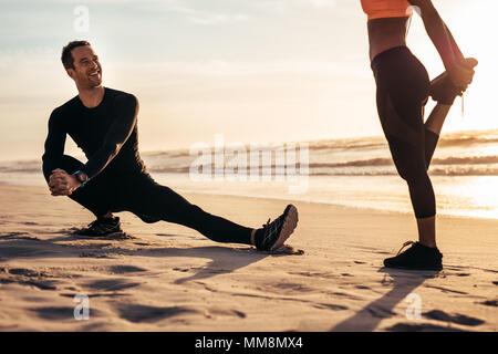 I giovani che esercitano sulla spiaggia di mattina. Runner di stiramento e di riscaldamento lungo la riva del mare e aventi una chat. Foto Stock