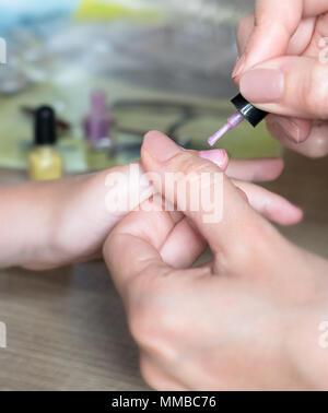 La mamma l'applicazione di smalto per unghie a sua figlia. Attività di divertimento a casa o ragazza festa di compleanno. Foto Stock