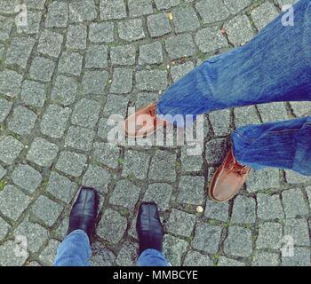 Gambe con scarpe da donna e uomo su una strada asfaltata di sfondo, vista dall'alto Foto Stock