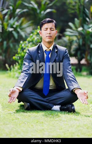 Una Business maschio erba seduta pratica Yoga Padmasana meditazione In-Garden Foto Stock