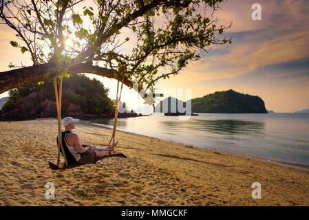Giovane uomo gode di tramonto su un altalena su una spiaggia in Thailandia