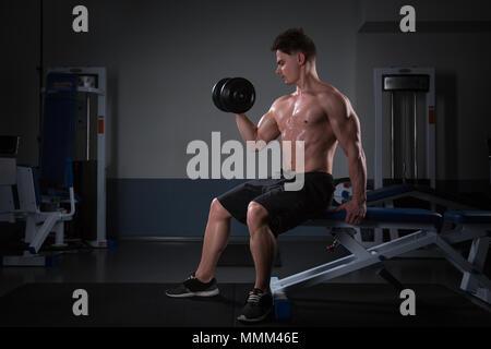 Bel giovane uomo in pantaloncini corti, facendo esercizi per bicipite, su uno sfondo scuro in studio. atleta con manubri presso la palestra al buio Foto Stock