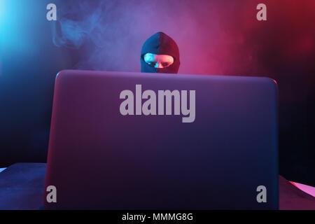 Arrabbiato hacker in tuta di rubare i dati dal computer portatile illuminato dal rosso e la luce blu Foto Stock