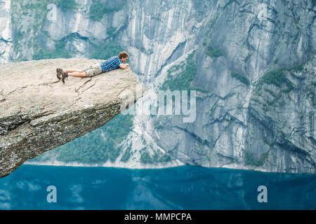 Odda, Norvegia - 04 agosto 2014: il giovane uomo su roccia aggrappato al bordo di una scogliera e guardando verso il basso nelle montagne della Norvegia. Le attrazioni naturali di Tr Foto Stock