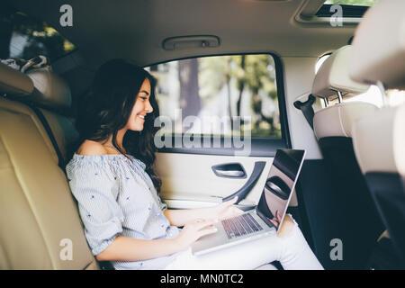 Bella donna d'affari sta usando un computer portatile mentre è seduto sul sedile posteriore in auto