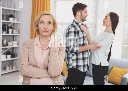 Età infelice donna in piedi nel soggiorno Foto Stock