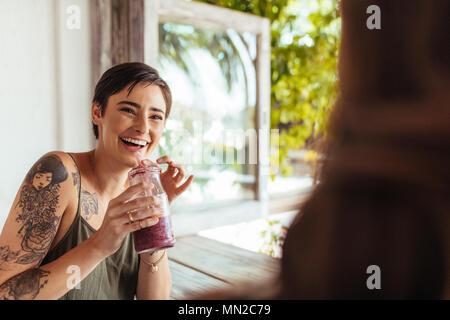 Donna che mantiene un smoothie jar a parlare con il suo amico in un ristorante. Donna con tatuaggio a portata di mano presso un ristorante di bere succo di frutta. Foto Stock