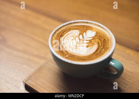 Close up cappuccino calda tazza di caffè con forma di cuore latte art sulla tavola di legno al cafe,tono Drak filtro,cibi e bevande Foto Stock