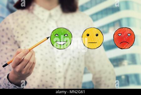 Giovane donna close up tenere una matita in mano scegliendo faccina sorridente rating. Servizio clienti eccellente concetto. Foto Stock