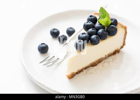 Fetta di cheesecake con mirtilli e foglia di menta su bianco. Vista ingrandita, il fuoco selettivo. New York cheesecake Foto Stock