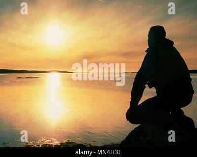 Uomo solitario escursionista si siede da solo sulla costa rocciosa e godersi il tramonto. Vista sulla scogliera rocciosa di oceano libero