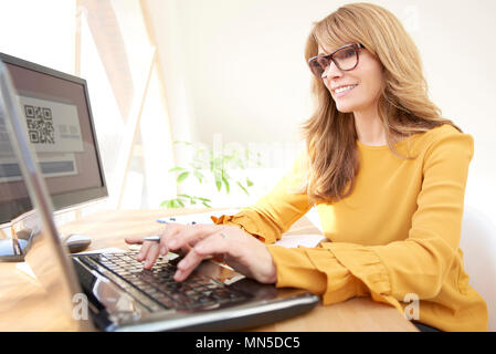 Sorridente imprenditrice maturo digitando su laptop mentre è seduto alla scrivania e lavorando in ufficio.