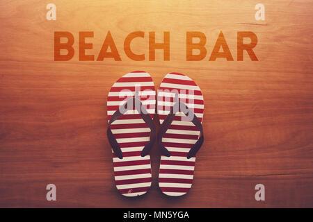 Bar sulla spiaggia e sandali infradito su sfondo di legno, vacanze estate Concetto di vacanza Foto Stock