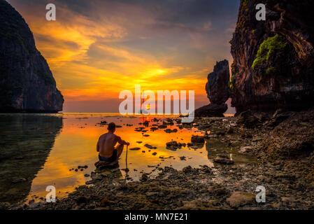 Ragazzo giovane gode di tramonto spettacolare al Maya Beach in Thailandia