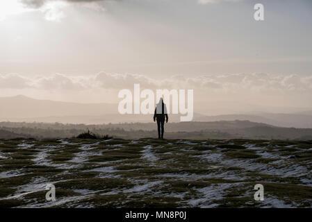 Una solitaria donna in piedi nella parte inferiore di fieno Bluff in Montagna Nera la visualizzazione del tardo pomeriggio luce su Herefordshire Foto Stock