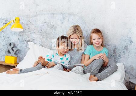 Bella madre è la lettura di una storia ai suoi figli Foto Stock