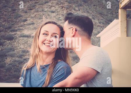 Amore sussurro segreto e di concetto per un giovane uomo e donna all'aperto sulla terrazza. vintage filtro per la scena romantica. bella bionda demale sorridente. Foto Stock