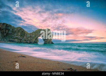 Il sole sorge oltre la Manica a Durdle porta sul Jurassic Coast in Dorset Foto Stock