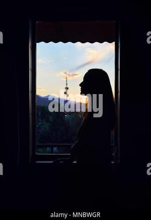 Silhouette di donna bella vicino alla finestra a hotel con sunrise sky in Kirghizistan Foto Stock