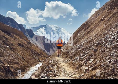 Escursionista in maglietta arancione con zaino camminando sul sentiero con vertice nevoso a sfondo Foto Stock