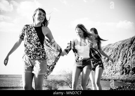 Tre giovani donne amici camminare insieme su un muro vicino alla spiaggia in Tenerife. Godetevi la vacanza sotto un cielo blu con sole giallo. Le mani con le mani. Foto Stock