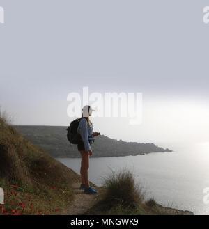 Giovane donna in piedi che guarda al mare, indossa pantaloncini uno zaino e tappo di picco. Ella è in alto guardando verso il basso