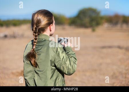 Adorabile bambina in Sud Africa safari con tazza di cioccolata calda guardando le zebre su una distanza Foto Stock