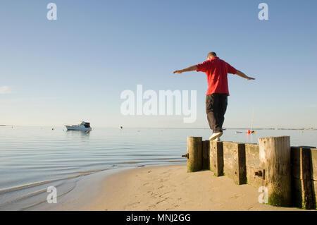 Un uomo di bilanciamento sulla barriera di legno in una bella e tranquilla posizione seashore. Foto Stock