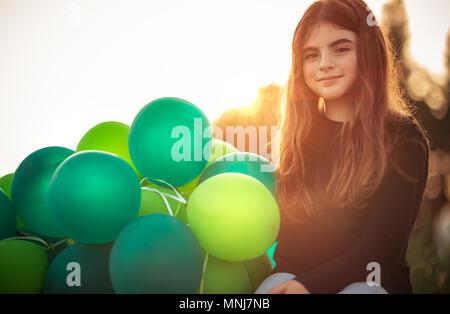 Ritratto di una incantevole piccola ragazza seduta nel parco con la pila di verde palloncini aria all'aperto in serata dolce della luce del sole, festeggia il compleanno, preparati Foto Stock