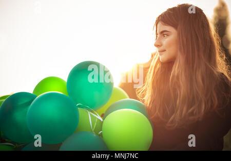 Ritratto di una ragazza carina all aperto con grande pila di aria verde palloncini, si prepara a celebrare la festa di compleanno, felice infanzia spensierata Foto Stock
