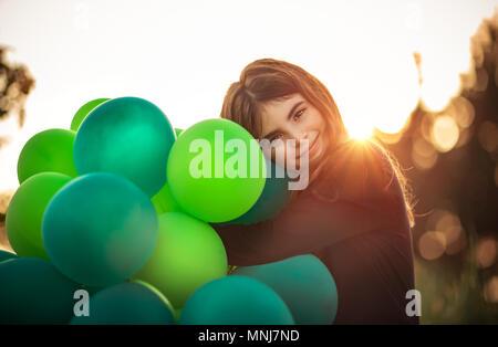Ritratto di una bella ragazza sorridente all'aperto avvolgente grande pila di aria verde palloncini, si prepara a celebrare la festa di compleanno, felice infanzia spensierata Foto Stock