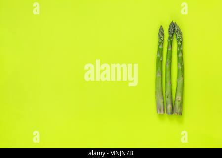 Bella arte cibo sfondo. I germogli di asparagi sul verde brillante superficie. Foto Stock