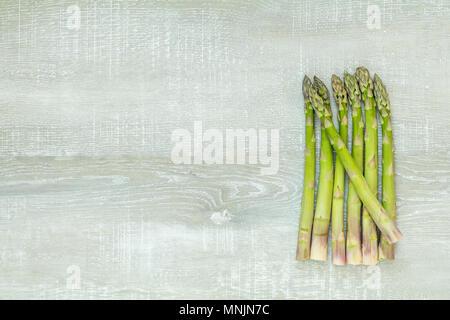 Bella arte cibo sfondo. Gli asparagi germogli di luce sulla superficie di legno. Foto Stock