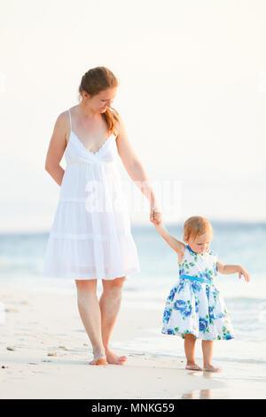 Foto verticale della giovane madre e la sua adorabile bambina sulla spiaggia al tramonto Foto Stock