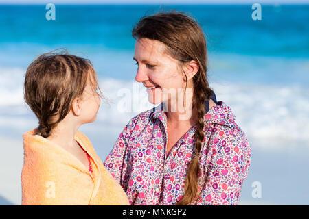 Madre e figlia coperti con un asciugamano in spiaggia, madre e figlia sulla spiaggia tropicale durante le vacanze estive Foto Stock