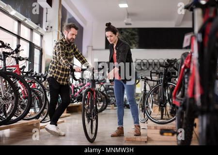 Titolare di una piccola azienda che serve il cliente in un negozio bike Foto Stock