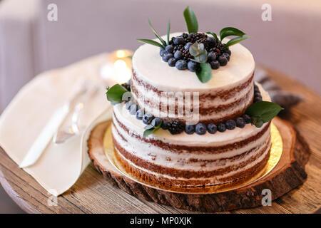 Il matrimonio o la torta di compleanno con frutti di bosco. Torta dolce sul banchetto nel ristorante. Foto Stock