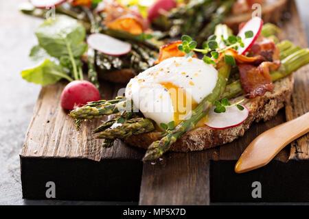 Gli asparagi e pancetta bruschetta con uovo in camicia Foto Stock