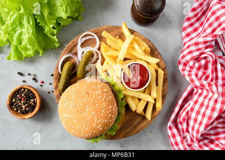 Burger con sesamo, patatine fritte e sottaceti e insalata di lattuga. Vista superiore della casalinga hamburger di manzo con patate fritte e sottaceti. Posizione orizzontale Foto Stock