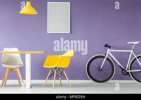 Minima, interni moderni con un bianco e giallo sedia, una bicicletta, una tabella vuota e appeso un lampada gialla contro sfondo viola parete con una simulazione Foto Stock
