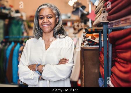 Sorridente donna matura in piedi nel suo tessuto colorato shop Foto Stock
