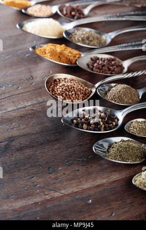 Spezie differenti in cucchiai su un vecchio sfondo di legno.