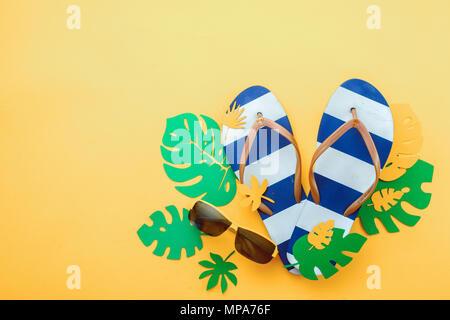La vacanza estiva laici piatto con foglie tropicali, occhiali da sole e spiaggia flip-flop su un soleggiato sfondo giallo con spazio di copia Foto Stock