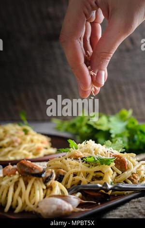 Una donna irrora un formaggio parmigiano pasta di gamberi e cozze in una salsa cremosa. Cucina italiana Foto Stock