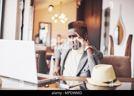 Malinconici afro american bello scrittore professionista di articoli popolari in blog vestito in abiti alla moda e bicchieri riflettendo su una nuova storia la correzione di bozze il suo copione da notebook in seduta cafe Foto Stock